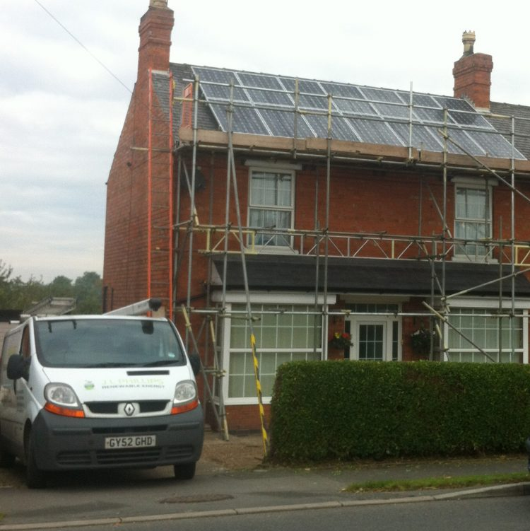 image of scaffolded home with solar panels on roof
