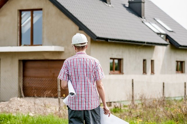 image of construction worker standing outside a house for external wall insulation