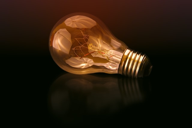 energy efficiency myths, light bulb placed on darker surface