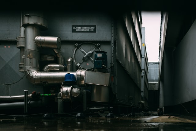 Leaky Boiler Problems; A boiler with complicated, huge pipes installed outside a building.